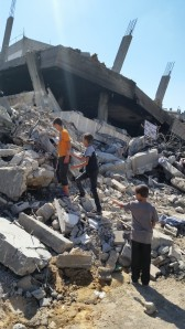 Palestinian children climb in rubble.