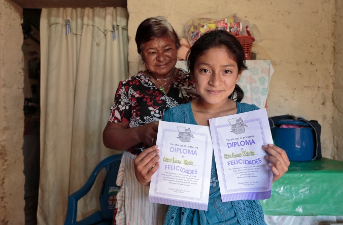 Mayra Martinez, 11, and her grandmother Lucía Mancía, 62, showing her math and language diplomas from the Peer to Peer Tutoring program given by her tutor, Elías Fabricio. Photo by Oscar Leiva/Silverlight for Catholic Relief Services