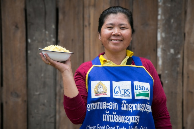 Hongkham Phengsaphone, age 36, holds a bowl of lentils at the Nahangnoy Primary School, where CRS' LEAPS program provides students with a free school lunch. Photo by Jim Stipe/Catholic Relief Services