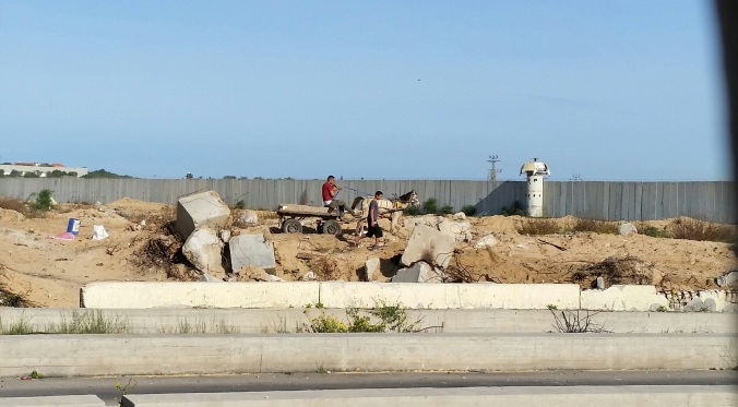 "Man in Gaza with donkey cart in ""no man's land"" gathers bits of concrete and iron rods"