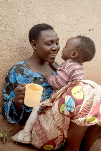 Jeanne Uwimbabazi smiles at her daughter Elissa Izibyose while feeding her porridge during a health and nutrition screening near Buruba Village, Muhanga District, Rwanda. Photo by Laura Elizabeth Pohl for Catholic Relief Services