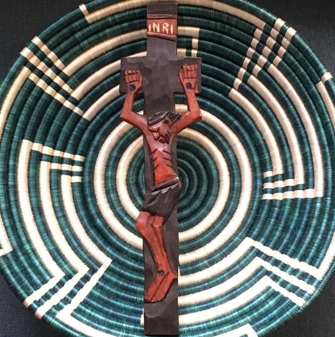 A carved wooden crucifix sits atop a green and white woven basket from Rwanda