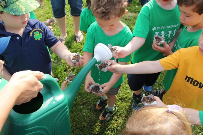 preschool children at a Catholic school use a watering can to water seedlings as they learn about Care for creation