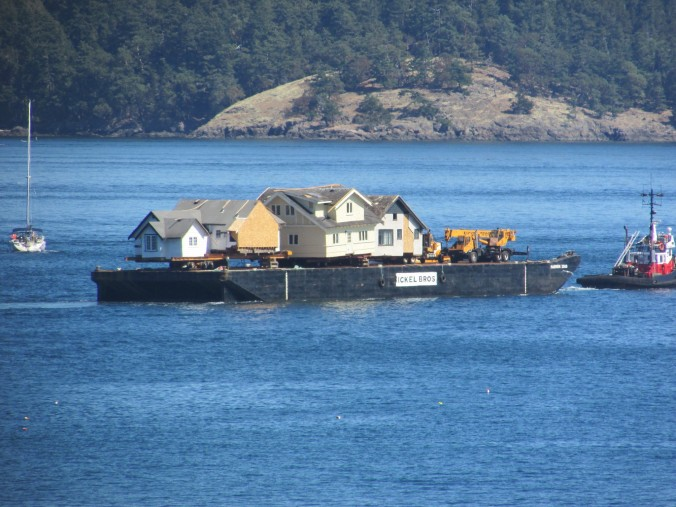 a barge carries a large home across the sea