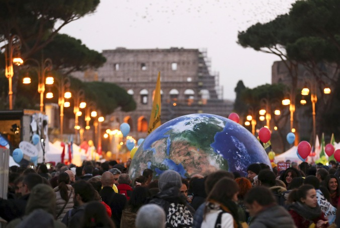 Protesters carry a globe-shaped balloon in front of Rome's Colosseum during a Nov. 29 rally, the day before the start of the U.N. climate change conference in Paris. (CNS photo/Alessandro Bianchi, Reuters) See COP21-VATICAN-PAROLIN Dec. 1, 2015.