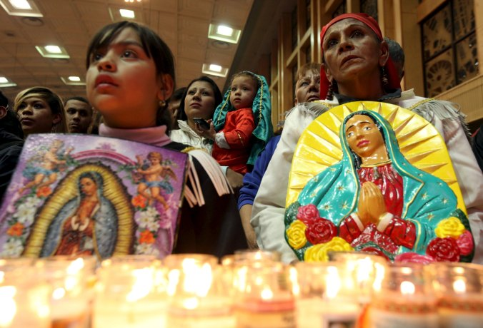 Pilgrims hold up images of Our Lady of Guadalupe during an annual pilgrimage in her honor (CNS photo/Jose Luis Gonzalez, Reuters)