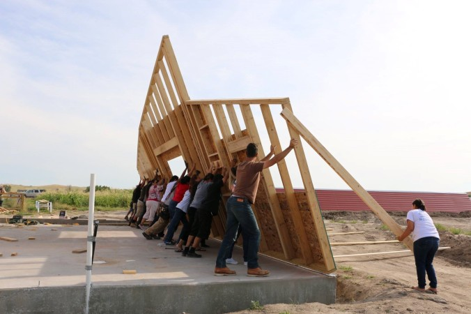 A team of people push up a frame of a wall on a cleared lot