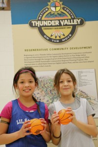 Two young Lakota girls in athletic gear and holding small basketballs smiling