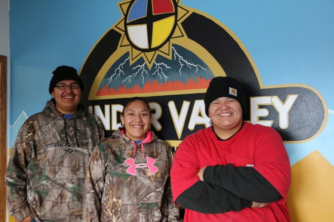 Three young adults smile in front of a Thunder Valley CDC sign